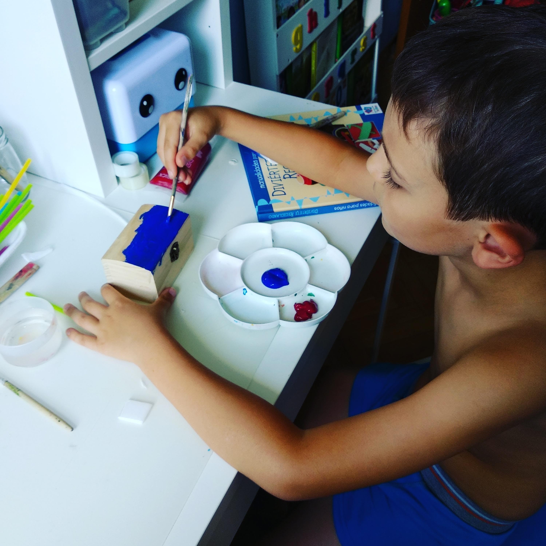 niño sentado a mesa pintando una caja