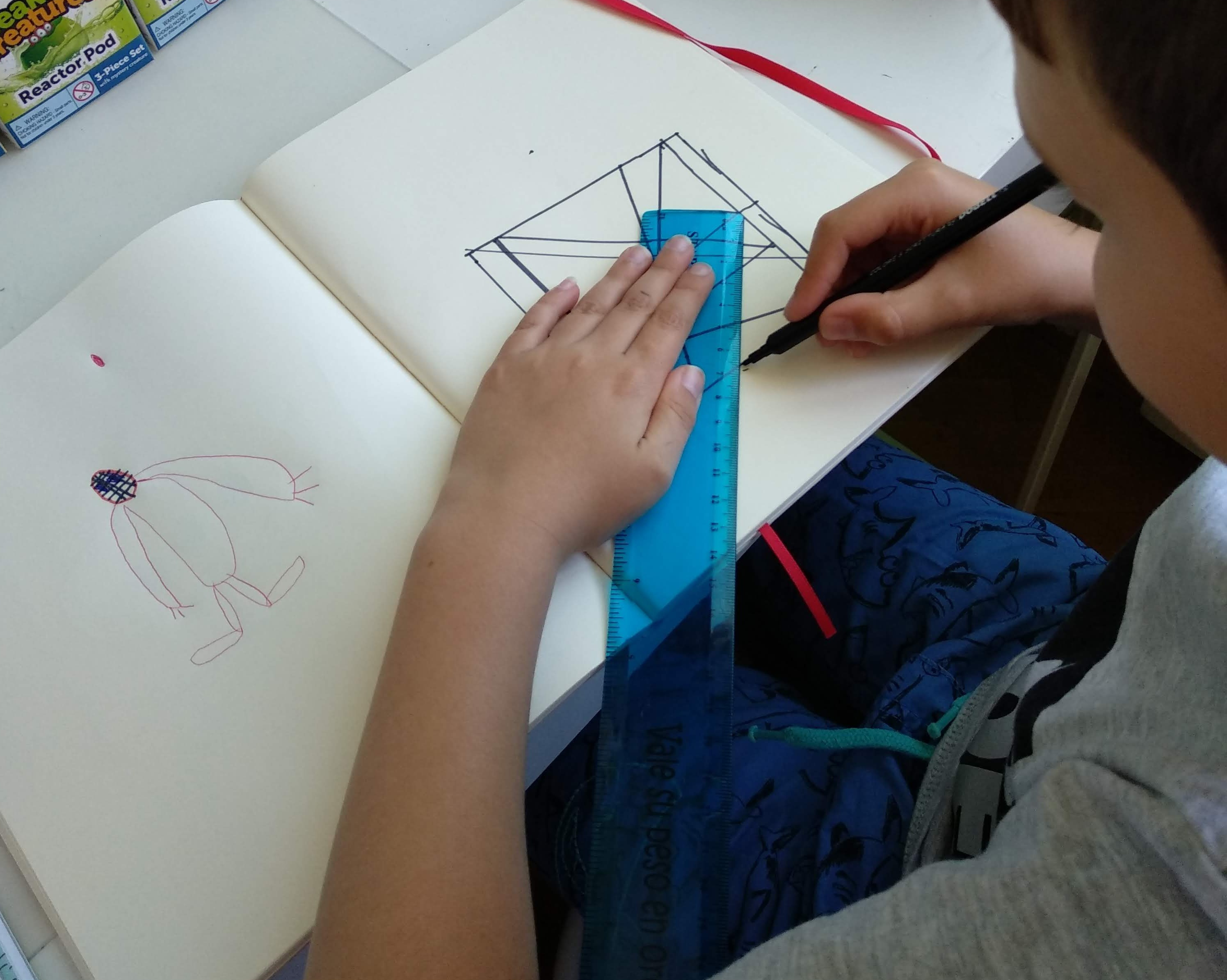 niño usando regla sobre un cuaderno trazando rectas